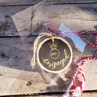 wood slice ornament that says engaged with an illustration of a diamond ring and the date in gold in a clear gift box with red and white string