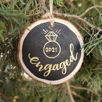 wood slice ornament that says engaged with an illustration of a diamond ring and the date in gold hanging in a tree