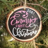 rustic wood slice ornament that says baby's name first Christmas 2020 hanging on a tree