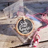 rustic wood slice ornament that says our first home in white hand lettering and a little house doodle with 2020 in a clear gift box with red and white string