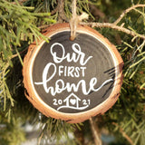 rustic wood slice ornament that says our first home in white hand lettering and a little house doodle with 2020 hanging in a tree