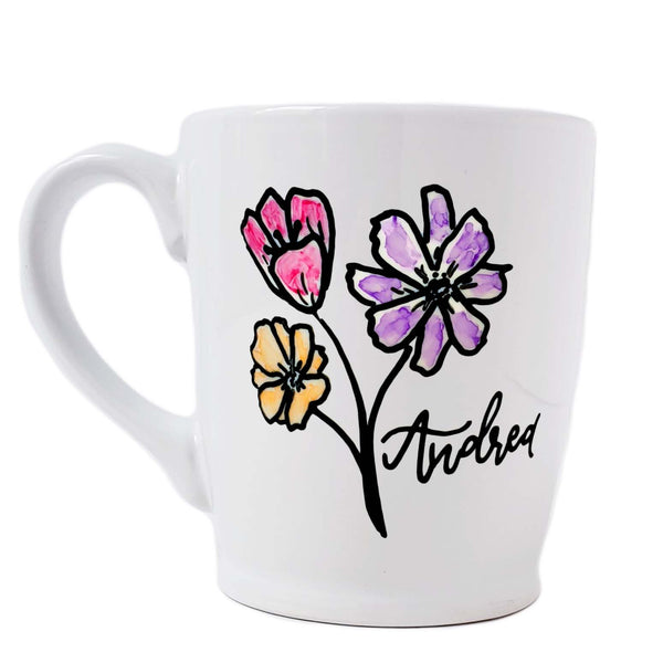 16 oz hand painted white ceramic coffee mug with 3 flower doodles, one pink, one purple and one orange with a first name in black hand lettering