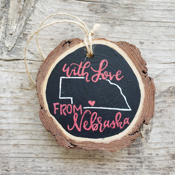 rustic wood slice ornament that says with love from nebraska in red hand lettering and an outline of the state of nebraska in white