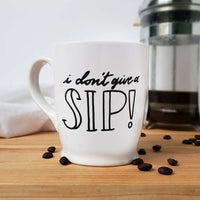 16 oz hand painted white ceramic coffee mug that says i don't give a sip in black hand lettering shown with scattered coffee beans and a french press and floursack towel in the background