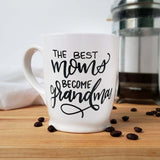 16 oz hand painted white ceramic coffee mug that says the best moms become grandmas in black hand lettering shown with  scattered coffee beans  and a french press and  floursack towel in the background