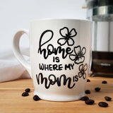 White 160z mug with hand painted design that says home is where my mom is with floral doodles in black
