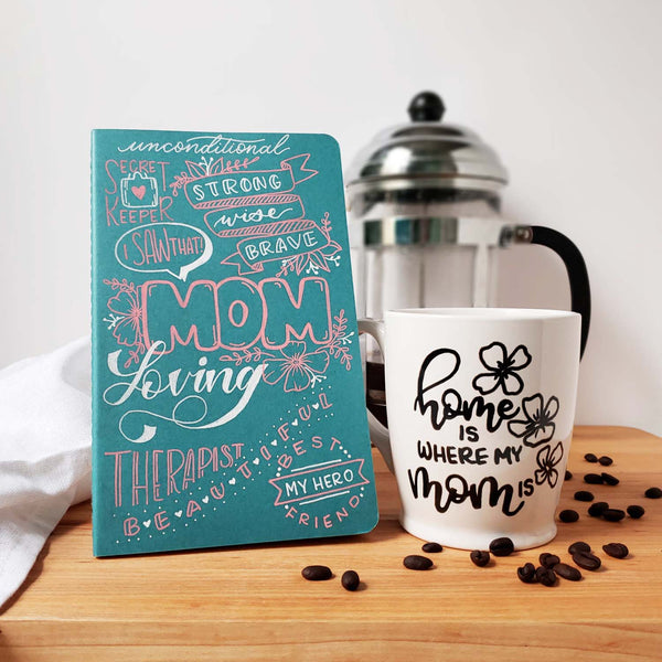 Mother's Day gift set including a hand painted mother's day journal and a hand painted mug that says home is where my mom is shown with scattered coffee beans, french press and white towel in the background and