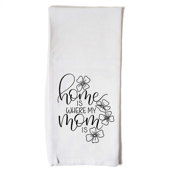 Hand lettered floursack kitchen towel in white that says home is where my mom is with floral doodles in black