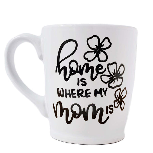 16 oz hand painted white ceramic coffee mug that says home is where my mom is in black hand lettering with 3 flower doodles
