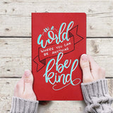 hands holding hand painted journal that says in a world where you can be anything be kind in turquoise, white, black lettering