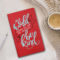 hand painted journal that says in a world where you can be anything be kind in turquoise, white, black lettering with a blanket, coffee and pen