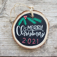rustic wood slice ornament that says merry Christmas in white hand lettering 2020 in red and green and evergreen and berry doodles in green and red