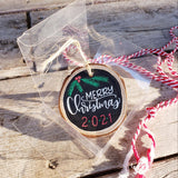 rustic wood slice ornament that says merry Christmas in white hand lettering 2020 in red and green and evergreen and berry doodles in green and red in a clear gift box