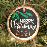 rustic wood slice ornament that says merry Christmas in white hand lettering 2020 in red and green and evergreen and berry doodles in green and red hanging on a tree