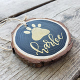 rustic wood slice ornament that says your pet's name hand lettered in gold with a paw print in gold