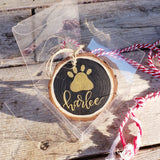 rustic wood slice ornament that says your pet's name hand lettered in gold with a paw print in gold in a clear gift box