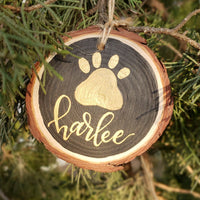 rustic wood slice ornament that says your pet's name hand lettered in gold with a paw print in gold hanging from a tree