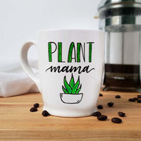 16 oz hand painted white ceramic coffee mug that says Plant Mama in black and green hand lettering with a doodle of a green succulent in a white pot shown with scattered  coffee beans and a french press and floursack towel in the background
