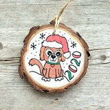 hand painted wood slice ornament with a brown puppy with a red santa hat and snowflakes painted all around