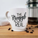 16 oz hand painted white ceramic coffee mug that says the struggle is real in black hand lettering shown with scattered coffee beans and a french press and floursack towel in the background