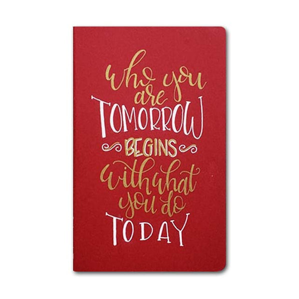 hand painted journal that says who you are tomorrow begins with what you do today in gold and white lettering on a cranberry journal