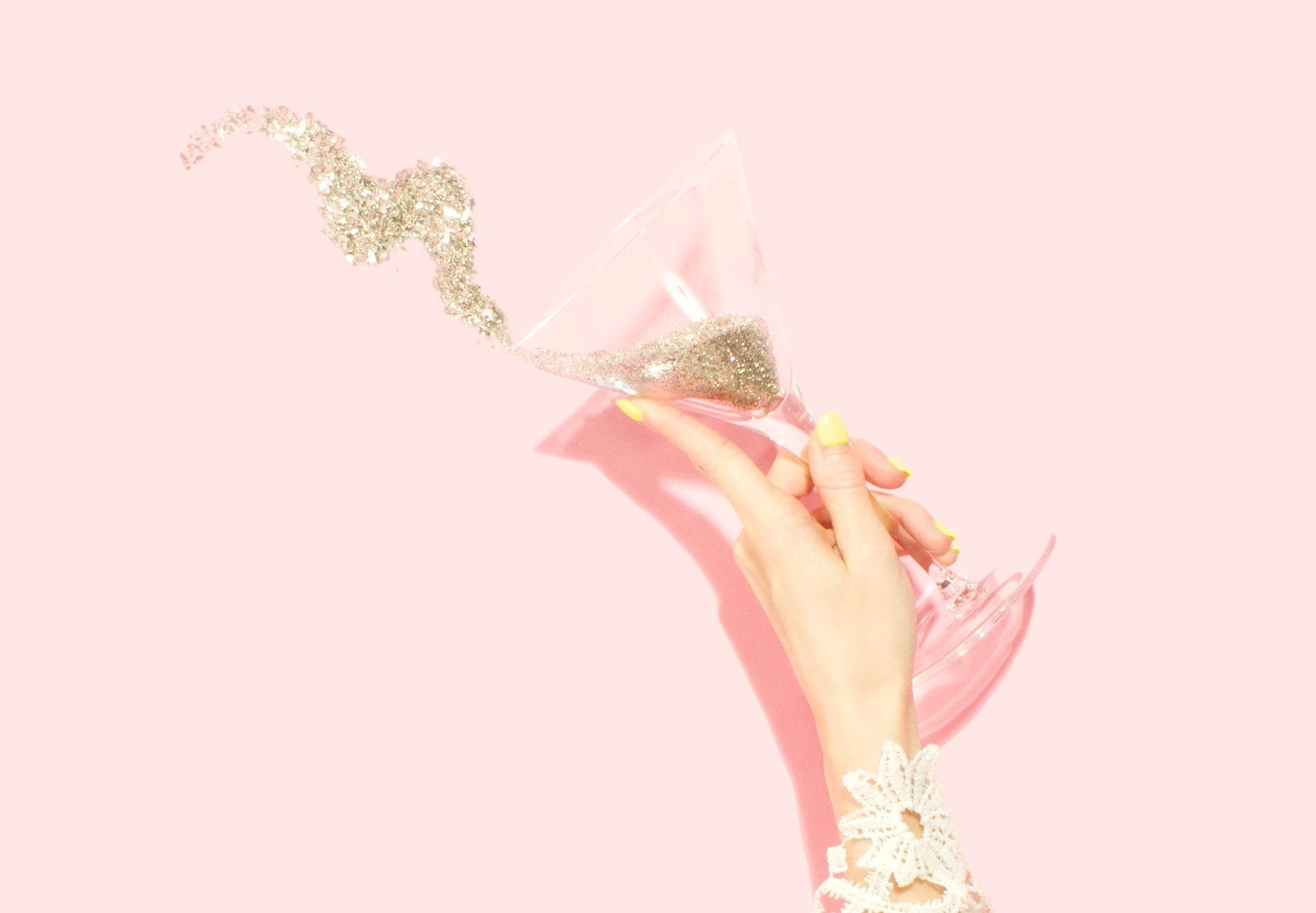 hand with sparkle tipping out of martini glass on pink background