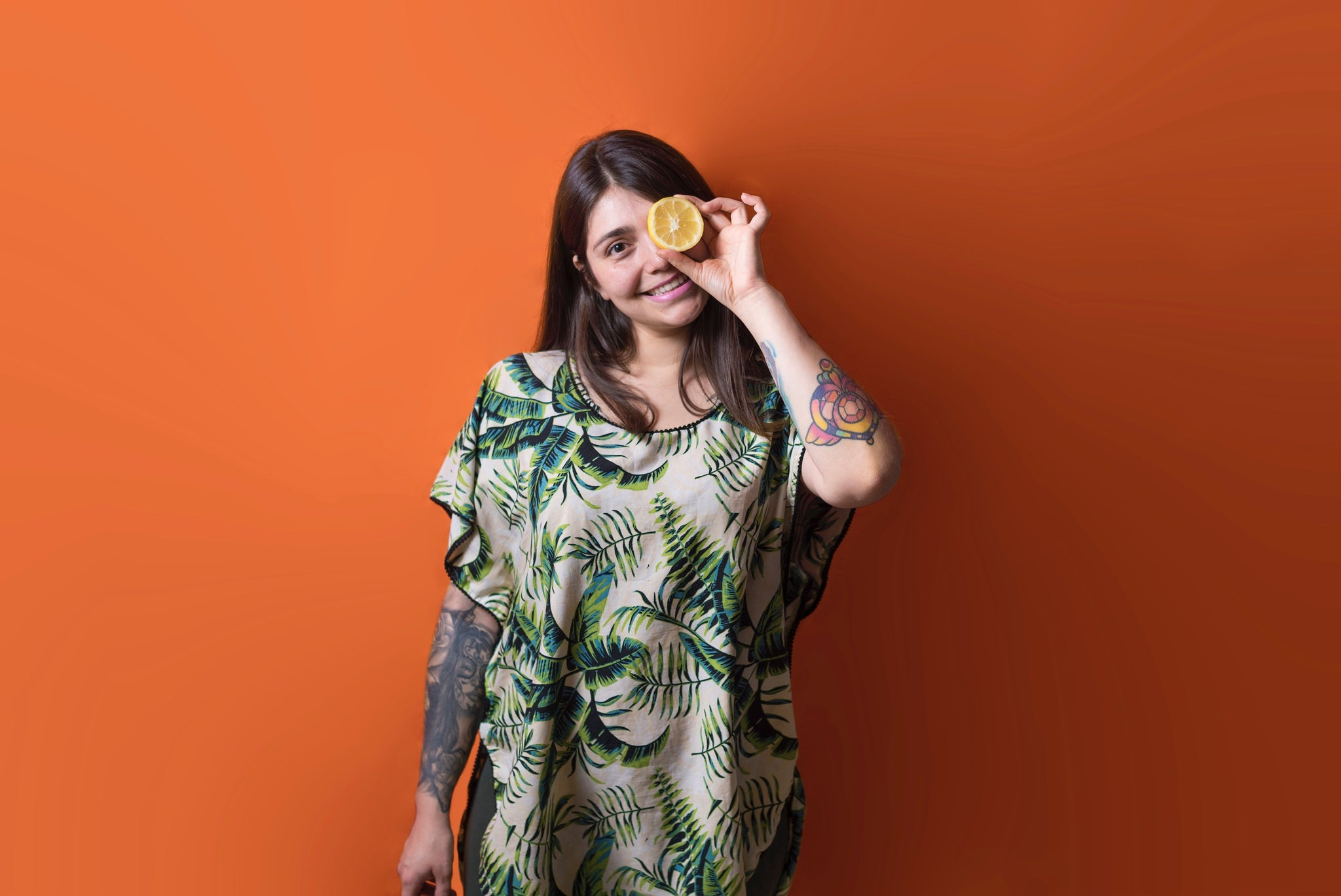 woman holding citrus over one eye