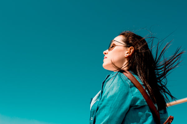 woman in a denim jacket with dark hair blowing in the breeze under a blue sky
