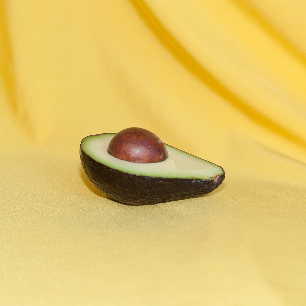 half an avocado with pit on a yellow fabric background