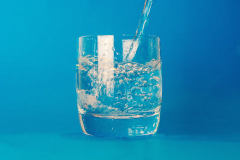 water pouring into drinking glass on blue background