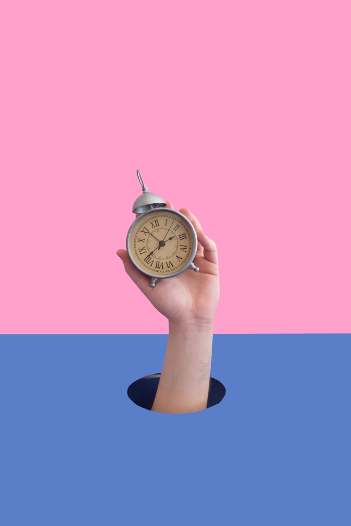 hand popping up from hole holding alarm clock against pink and blue background