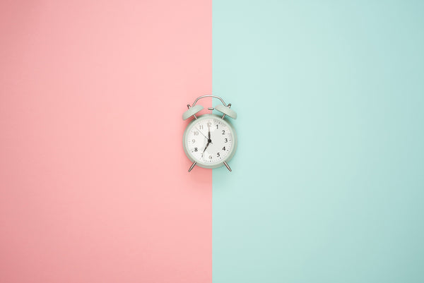 alarm clock on a pink and blue background