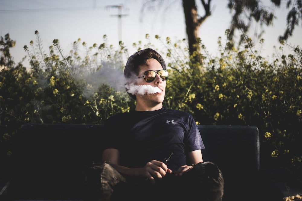 Man exhaling ecigarette in front of flowers