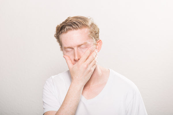 man yawning into his hand with closed eyes