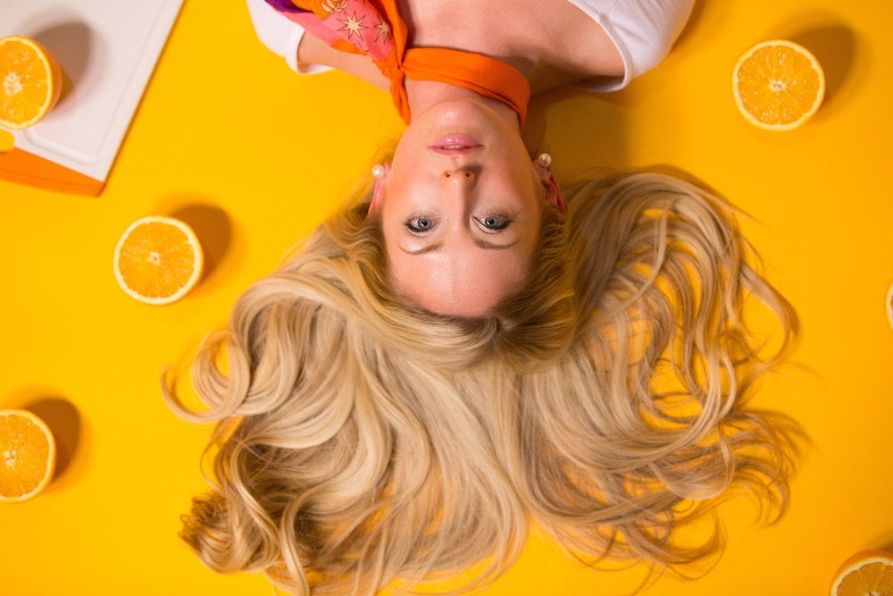 woman on the ground with blonde hair and oranges