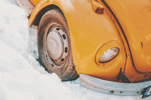 old yellow vw beetle tire in snow