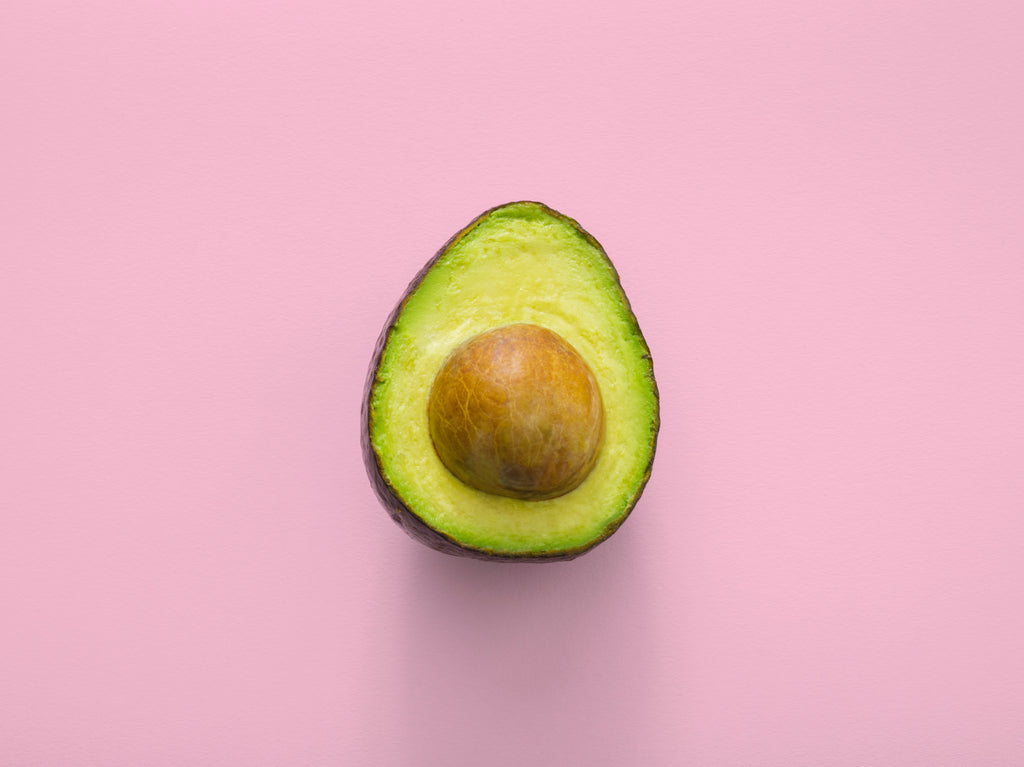 half avocado on a pink background