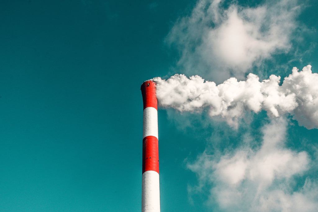 red and white smoke stack emitting steam under a blue sky