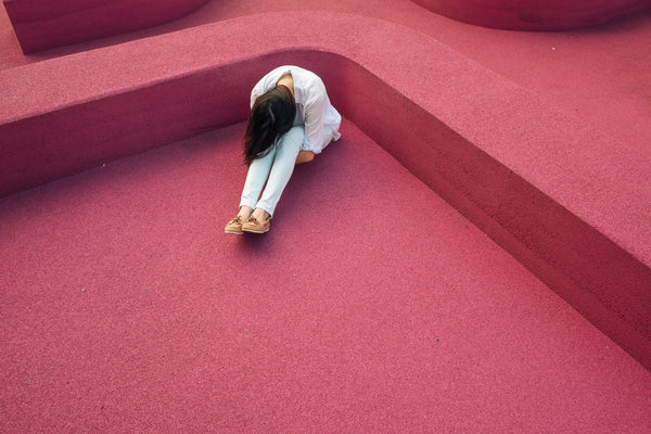 woman on a red floor with her head between her knees