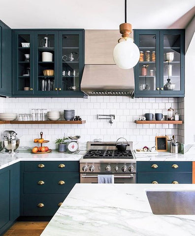 A view of a sustainable kitchen with navy cabinets, white countertops, and brass light fixtures