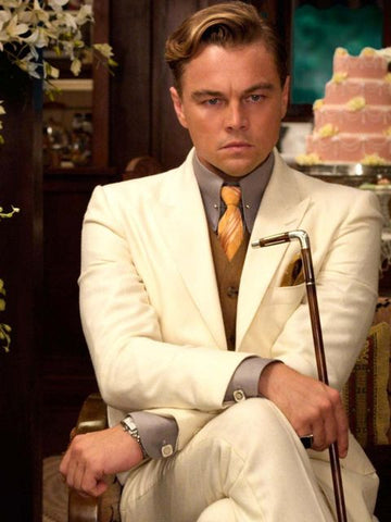 Leonardo Dicaprio as Jay Gatsby in the Great Gatsby wearing a cream coloured suit and yellow tie while he sits in a chair holding a can