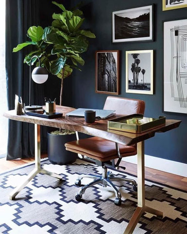 A minimal office with navy walls and a wooden desk with a laptop on it