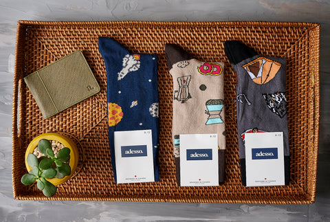Three pairs of bold, patterned socks on a wooden tray with a plant and leather bi-fold wallet