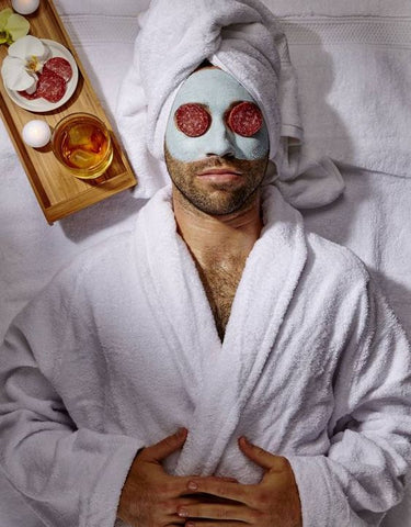 A man wearing a robe is laying down on a bed. He has a face mask on with two slices of pepperoni over his eyes. A whiskey and meat platter rest next to him on a tray.