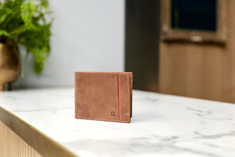 The Saddle Leather Brown Striped Adesso Man wallet sits upright on a white countertop