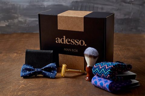 The Adesso Man Subscription Box with a tie, cardholder, safety razor, shaving brush, and two pairs of socks in front of it
