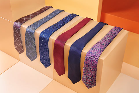 6 of Adesso's neckties are lined up on a brown table top