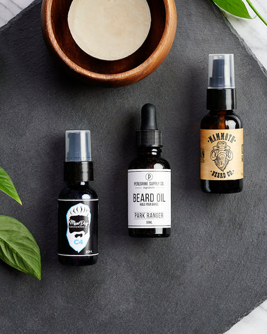three bottles of beard oil from different Canadian brands are lined up on a table