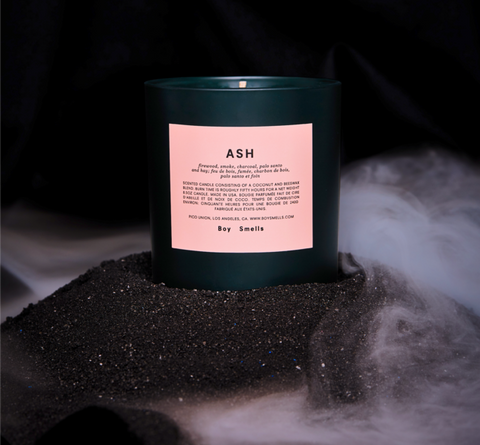 The Holiday Ash candle from Boy Smells in a dark green vessel with pink labelling. It is sitting on top of a mound of charcoal with smoke swirling around it