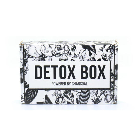 "a black and white floral cardboard box with the words ""detox box"" written across"